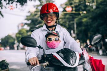 baby wearing pollution mask on scooter